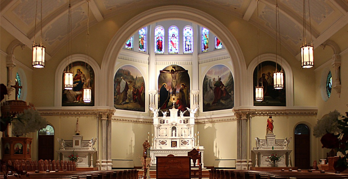 View of altar with triptych paintings and stained glass windows